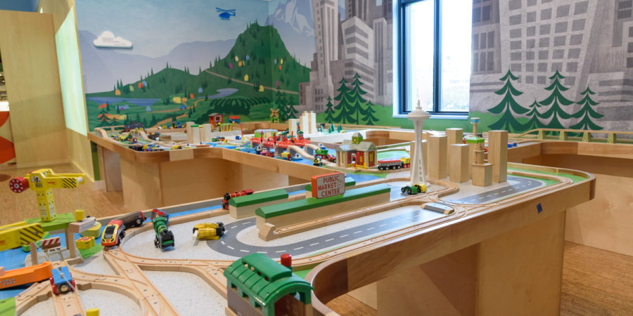 Room with train table and train set. Walls are painted with a mural of mountains and downtown skyline.